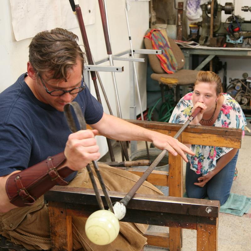 James assisting a visitor in glass blowing at Open Studios